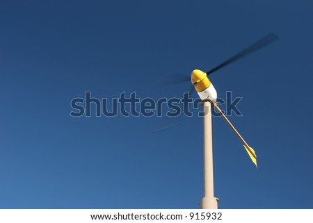 wind turbine with motion blur, against blue sky - stock photo