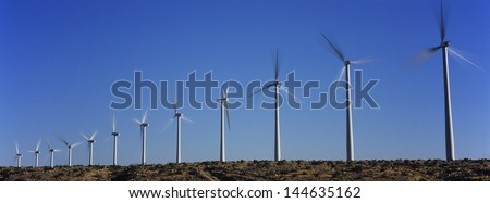 Wind turbines against blue sky - stock photo