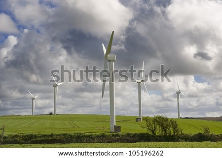 Wind turbines against the cloudy sky in Cornwall, UK. - stock photo