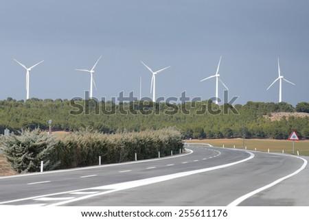 wind turbines along the road - stock photo