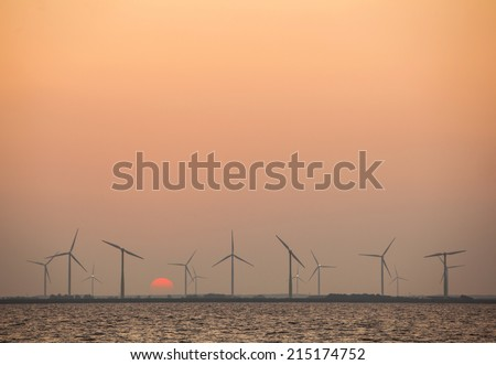 wind turbines and rising sun in colorful sky in the dutch province of flevoland - stock photo