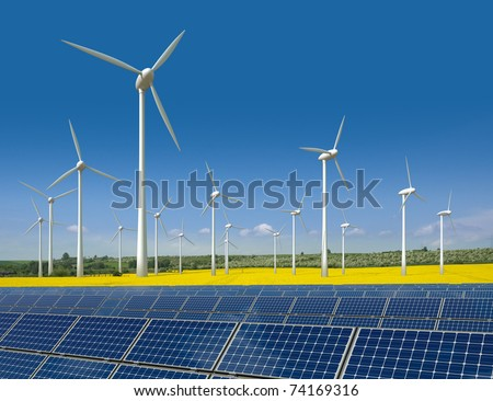 Wind turbines and solar panels in a rapeseed field - stock photo