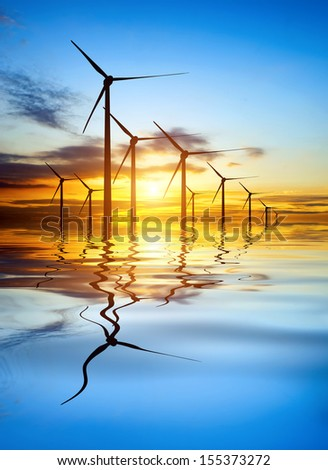 Wind turbines at dusk reflection scenery - stock photo