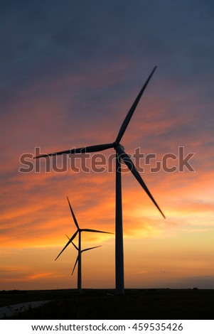 Wind turbines at sunset with motion blur on blades