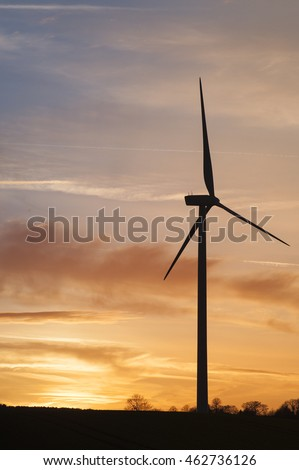 Wind turbines clean energy creation, large windmills designed to reduce global warming built on farmland showing dramatic sunset in background.