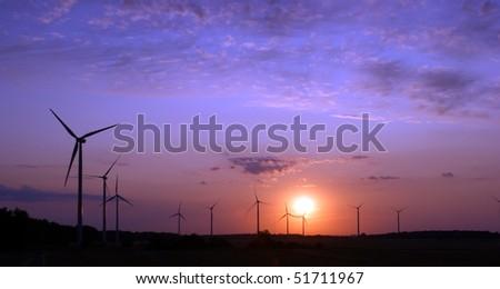 Wind turbines during sunset - stock photo