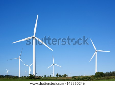 Wind turbines generating electricity against blue sky - stock photo
