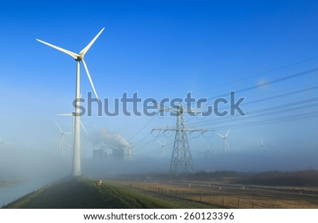Wind turbines generating sustainable energy on a foggy morning in an industrial area. - stock photo