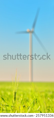 Wind turbines in a wheat field and clear sky - stock photo