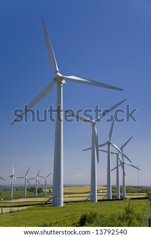 Wind turbines in a windfarm against a blue sky - stock photo