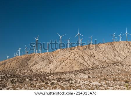Wind turbines in desert landscape - stock photo