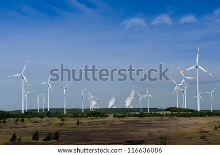 Wind turbines in front of a coal-fired plant - stock photo