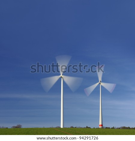 Wind turbines in movement against blue sky - stock photo