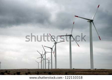 Wind turbines in row with stormy skies