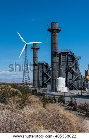 Wind turbines in the desert on a windy day near a power station - stock photo