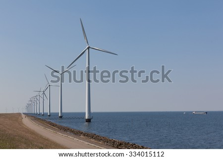 Wind turbines in the water with a clear blue sky - stock photo