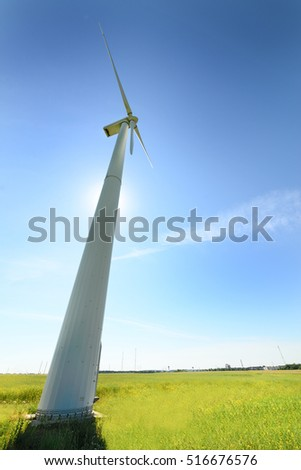 Wind turbines installed in the green field. Alternative clean energy. Sunny day. Blue sky.