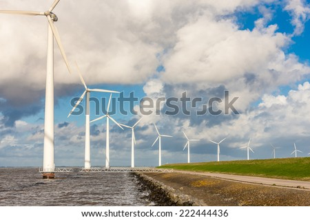 Wind turbines on a sea dike in holland - stock photo