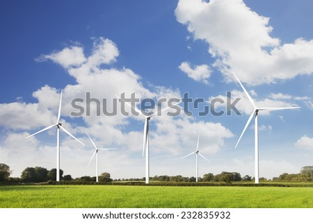 Wind turbines on green fields. - stock photo