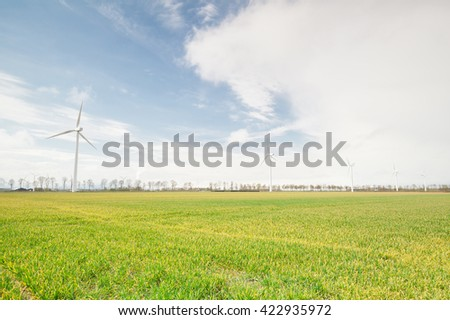 wind turbines on green sunny meadow and blue sky - stock photo