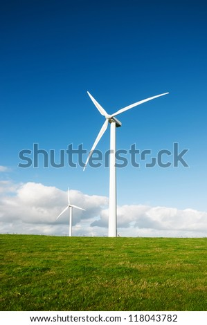 Wind turbines on the beautiful autumn meadow. - stock photo