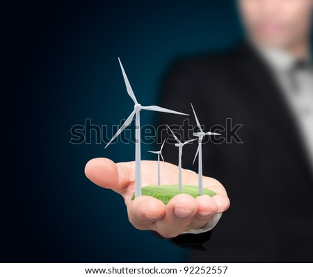Wind turbines on the hands businessman. - stock photo