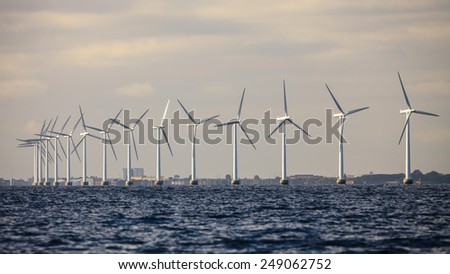 wind turbines power generator farm for renewable energy production along coast baltic sea near Denmark. Alternative green energy ecology. - stock photo