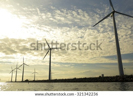wind turbines power generator farm for renewable energy production along coast baltic sea near Denmark at sunset /sunrise. Alternative green energy. ecology. - stock photo