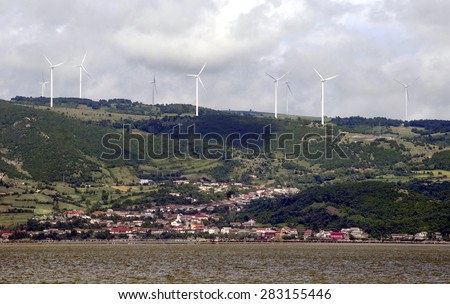 wind turbines power generator farm for renewable energy production along coast of Danube river - stock photo