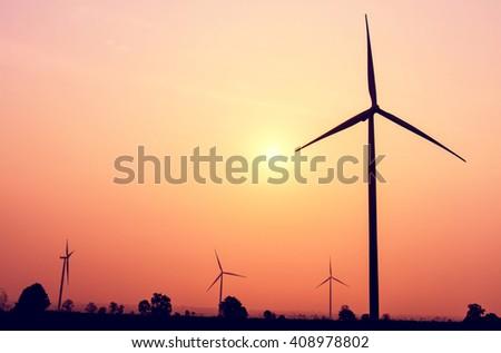 Wind turbines power generator on sunrise at farmer field - stock photo