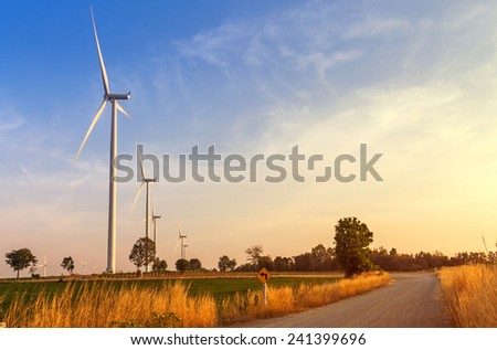 Wind turbines power generator on sunset at farmer field