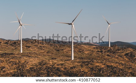 Wind turbines producing clean energy in a hilly landscape - stock photo