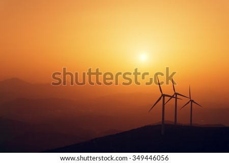 wind turbines silhouette on mountain at the sunset