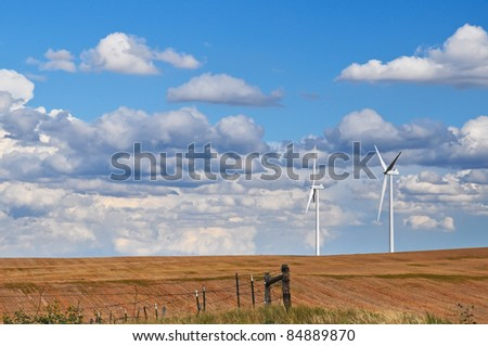 Wind turbines stand like friendly giants on the horizon against a beautiful blue and cloudy sky - stock photo