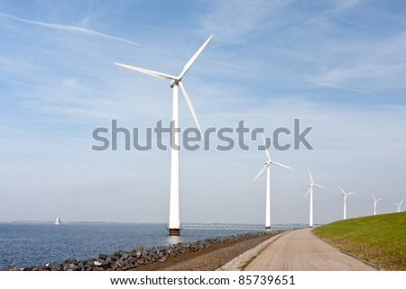 Wind turbines standing along the dyke in the Dutch sea - stock photo