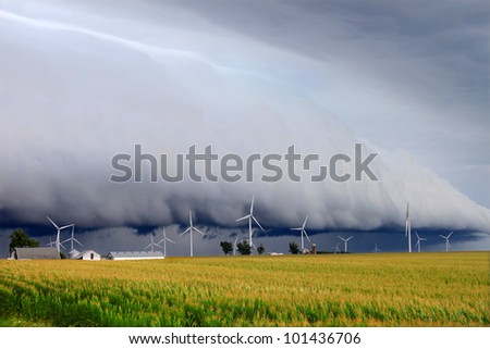 Wind turbines under a dark and ominous shelf cloud in northern Illinois - stock photo