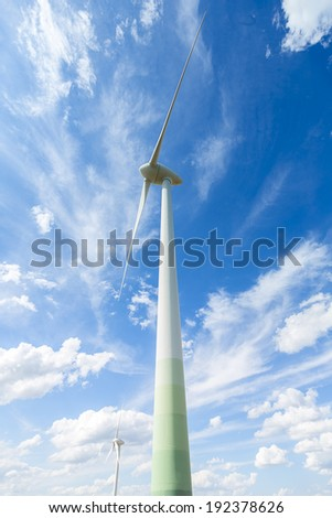 Wind turbines winpower on blue sky with clouds energy