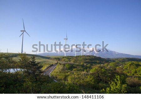 Wind turbines with a scenic snow-capped mountain