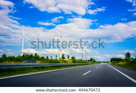 Wind turbines with highway and cars in summer  - stock photo