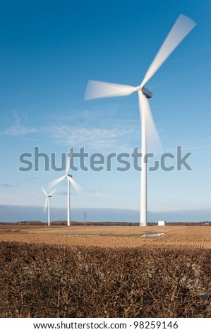 Wind turbines with motion blur vertical / Wind farm showing motion blur on rotating blades - stock photo