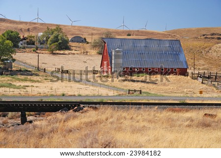 Wind Turbines with old red barn and farm - stock photo