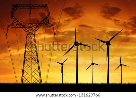 Wind turbines with power line in the sunset - stock photo