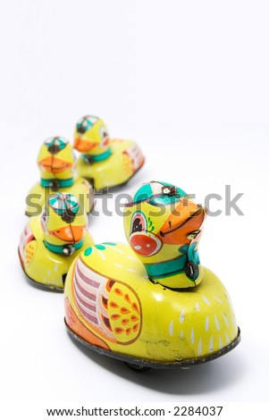 Wind up tin toy duck with three ducklings on white background. Narrow depth of field with duck in focus. - stock photo