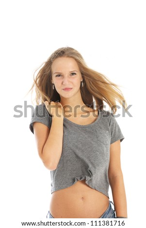 Windblown young woman Windblown young woman in casual jeans and top standing with the breeze blowing through her long blonde hair isolated on white