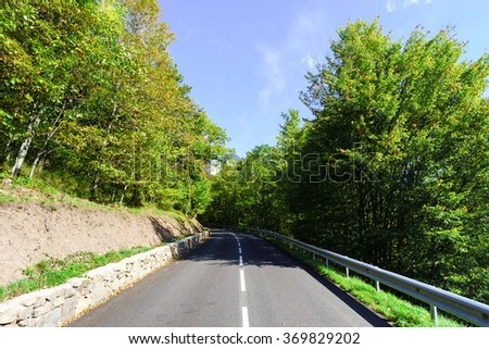 Winding asphalt road in countryside region of France, summer time - stock photo