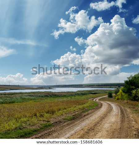 winding country road and clouds in blue sky - stock photo
