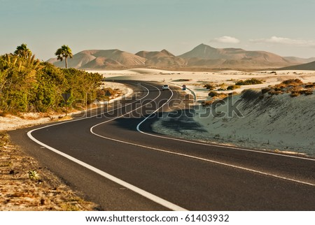 Winding desert road across the dunes of Corralejo, Fuerteventura, in the Canary Islands, Spain.