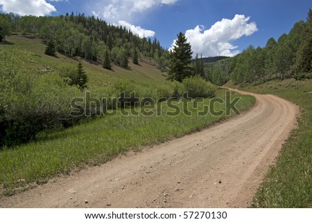 winding dirt lane ascending a mountain - stock photo