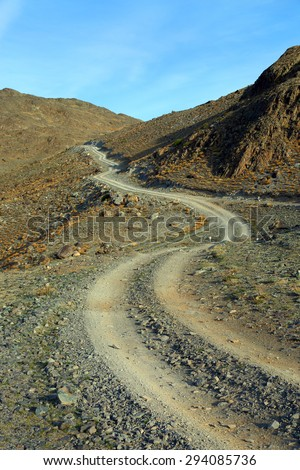 winding mountain road leading up - stock photo