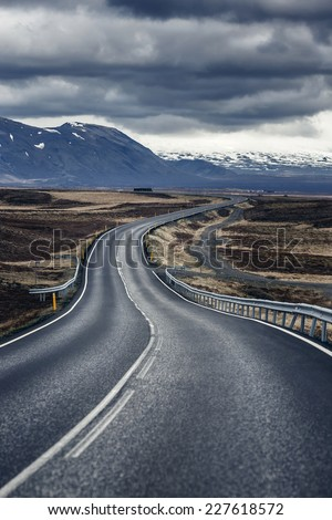 Winding mountain road next to Hvalfjordur fiord in Iceland - stock photo